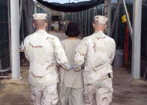 A prisoner at Guantanamo Bay escorted by two soldiers by Navy Petty Officer 1st Class Michael Billings [Public domain], via Wikimedia Commons